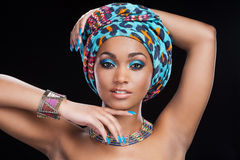 In traditional African style. Beautiful African woman in headscarf and jewelry posing against black background and looking at camera Royalty Free Stock Photo