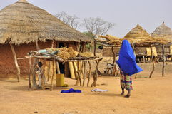 Traditional african village houses. With women wearing blue, Niger Royalty Free Stock Photo