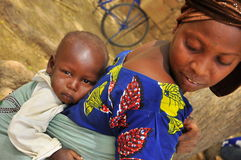 Traditional african women with baby on the back. Niger, West Africa, village Royalty Free Stock Image