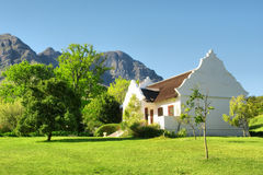 Traditional Cape Dutch house against mountains. Traditional Afrikaner house against mountains. Shot in Helderberg Mountains Nature Reserve, near Somerset West/ Royalty Free Stock Images