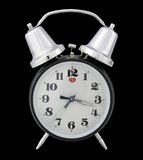 Traditional alarm clock (black background). Separated alarm clock Stock Image