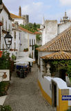 Typical Obidos Medieval Alley - Restaurant Terrace. Narrow street, with cobblestone ground, lined with typical portuguese houses, in medieval village of Obidos Stock Image