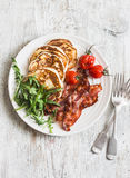 Traditional american breakfast - crispy bacon, pancakes with maple syrup, roasted tomatoes, arugula. On a light background Royalty Free Stock Photography