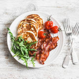 Traditional american breakfast - crispy bacon, pancakes with maple syrup, roasted tomatoes, arugula. On a light background Stock Image