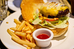 Traditional american burger, freshly french fries Royalty Free Stock Images