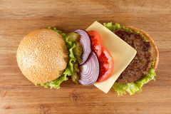 Traditional American cheeseburger. Meat, bun and vegetables close up. Ingredients traditional American cheeseburger. Meat, bun and vegetables close up Royalty Free Stock Photo