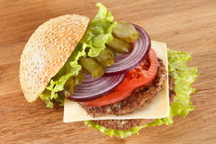 Traditional American cheeseburger. Meat, bun and vegetables close up Royalty Free Stock Photo