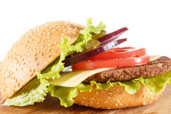 Traditional American cheeseburger. Meat, bun and vegetables close up Royalty Free Stock Photos