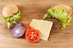 Traditional American cheeseburger. Meat, bun and vegetables close up Royalty Free Stock Images