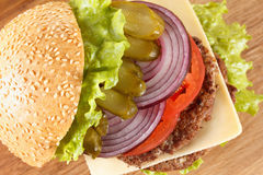 Traditional American cheeseburger. Meat, bun and vegetables close up Stock Photography