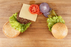 Traditional American cheeseburger. Meat, bun and vegetables close up. Ingredients traditional American cheeseburger. Meat, bun and vegetables close up Royalty Free Stock Images