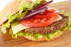 Traditional American cheeseburger. Meat, bun and vegetables close up Stock Image