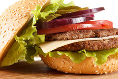Traditional American cheeseburger. Meat, bun and vegetables close up Royalty Free Stock Photography