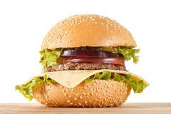 Traditional American cheeseburger. Meat, bun and vegetables close up. On white background Stock Photos
