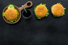 Traditional american food concept with burger on pan and drink on black background top view space for text.  royalty free stock photos