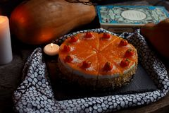 Traditional american fresh round bright orange tasty homemade pumpkin pie on decorative table with textil, pumpkins and candles li Stock Photos