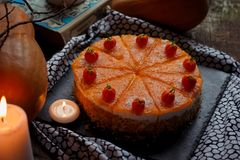 Traditional american fresh round bright orange tasty homemade pumpkin pie on decorative table with textil, pumpkins and candles li Stock Image