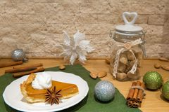 Traditional american pumpkin pie with whipped cream, whipped cream, cinnamon and almonds. Decorated with christmas green balls, b royalty free stock image