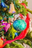 Traditional Antique Christmas Ornaments on Tree Branches. Vertical close-up image of colorful antique traditional Christmas tree ornaments and lights on branches Royalty Free Stock Image