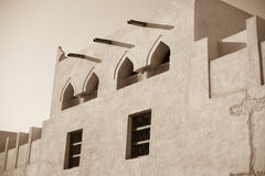 Traditional arabian house exterior. Exterior adobe wall of Isa bin Ali House, Muharraq, Bahrain showing arched windows, wooden window frames and water guttering Royalty Free Stock Photos