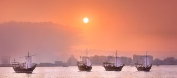 Traditional Arabic boats in Doha harbour, Qatar. Traditional Arabic Dhow boats in Doha harbour during orange sunset, Qatar Royalty Free Stock Image