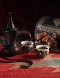 Traditional Arabic coffee. Arabic coffee cups, dates and rosary in traditional setting Stock Image