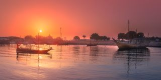 Traditional Arabic Dhow boats in Doha harbour. View during dramatic sunset, Qatar Stock Photography