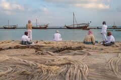 Traditional Arabic fishermen sitting and standing  on Katara beach with dhows in the water and clouds in the sky in background.