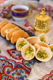 Traditional Arabic kataif crepes stuffed with cream and pistachios, prepared for iftar in Ramadan on paisley background Royalty Free Stock Images