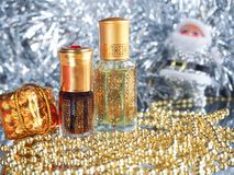 Traditional arabic perfume oil. Perfume oil fragrances in mini bottle on golden and silver  background. Holidays decoration. Chris. Traditional arabic perfume Stock Image