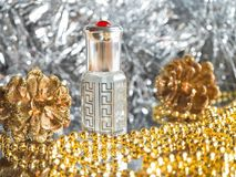 Traditional arabic perfume oil. Perfume oil fragrances in mini bottle on golden and silver  background. Holidays decoration. Chris. Traditional arabic perfume Royalty Free Stock Photo