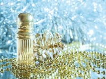 Traditional arabic perfume oil. Perfume oil fragrances in mini bottle on golden and silver  background. Holidays decoration. Chris. Traditional arabic perfume Royalty Free Stock Image
