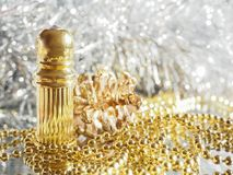 Traditional arabic perfume oil. Perfume oil fragrances in mini bottle on golden and silver  background. Holidays decoration. Chris. Traditional arabic perfume Stock Photos