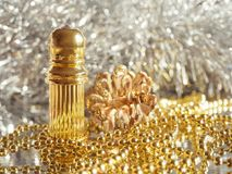 Traditional arabic perfume oil. Perfume oil fragrances in mini bottle on golden and silver  background. Holidays decoration. Chris. Traditional arabic perfume Stock Photography