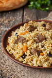 Traditional arabic spicy rice food with meat. Onion carrot and garlic. Served with fresh bread and vegetables on vintage dish on wooden background Stock Photography