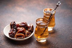 Traditional arabic tea and dry dates. Selective focus Royalty Free Stock Images