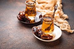 Traditional arabic tea and dry dates. Selective focus Royalty Free Stock Image