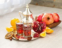 Traditional arabic tea with metal teapot and fruits. Tea with spices and pomegranate on a tray selective focus Stock Photo