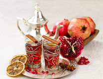 Traditional arabic tea with metal teapot and glasses. Tea with spices and pomegranate on a tray selective focus Royalty Free Stock Images