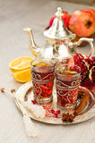 Traditional arabic tea with metal teapot and glasses vertical. Tea with spices and pomegranate on a tray selective focus Royalty Free Stock Images