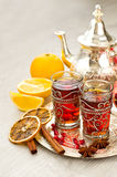 Traditional arabic tea with metal teapot and glasses vertical. Tea with spices and pomegranate on a tray selective focus Stock Images