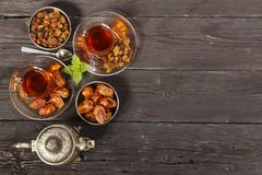 Traditional Arabic, Turkish Ramadan tea with dry dates and raisins on a wooden black table. Ramadan. Turkish fresh tea with dates. View from above Stock Photography