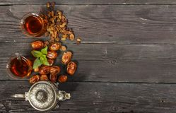 Traditional Arabic, Turkish Ramadan tea with dry dates and raisins on a wooden black table. Ramadan. Turkish fresh tea with dates. View from above Stock Images