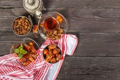 Traditional Arabic, Turkish Ramadan tea with dry dates and raisins on a wooden black table. Ramadan. Turkish fresh tea with dates. View from above Stock Photos