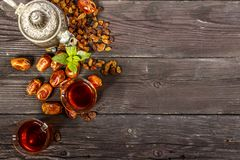 Traditional Arabic, Turkish Ramadan tea with dry dates and raisins on a wooden black table. Ramadan. Turkish fresh tea with dates. View from above Royalty Free Stock Image