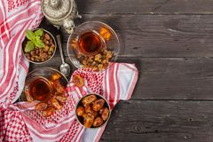 Traditional Arabic, Turkish Ramadan tea with dry dates and raisins on a wooden black table. Ramadan. Turkish fresh tea with dates. View from above Stock Image