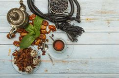 Traditional Arabic, Turkish Ramadan tea with dry dates and raisins on a wooden white table. A cup of tea on a white table.Turkish royalty free stock image