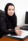 Traditional Arabic young woman at the office. With phone and documents Stock Photos