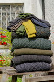 Traditional Aran knit sweaters and socks. Stack of chunky Irish wool cable knit and Aran winter sweaters plus socks in fall and winter colours in a pretty Irish Stock Image