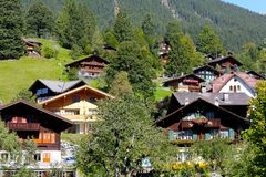 Traditional architecture of alpine houses. Grindelwald, Switzerland - September 21, 2017: Traditional architecture of alpine houses has been hidden between trees Stock Images
